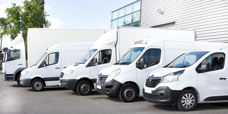 Varios Autos, Camionetas y Camiones en un Estacionamiento Listos para Hacer Entregas