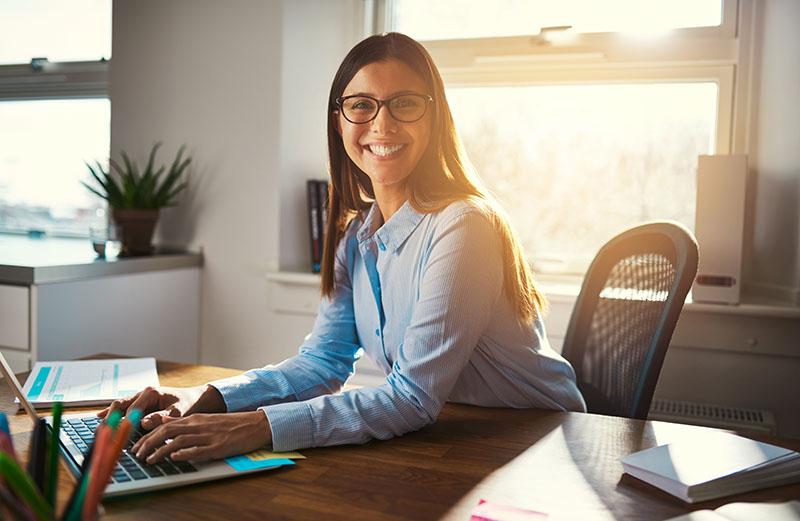 Joven Empresaria en su Escritorio Sonriendo - Paga Menos Insurance